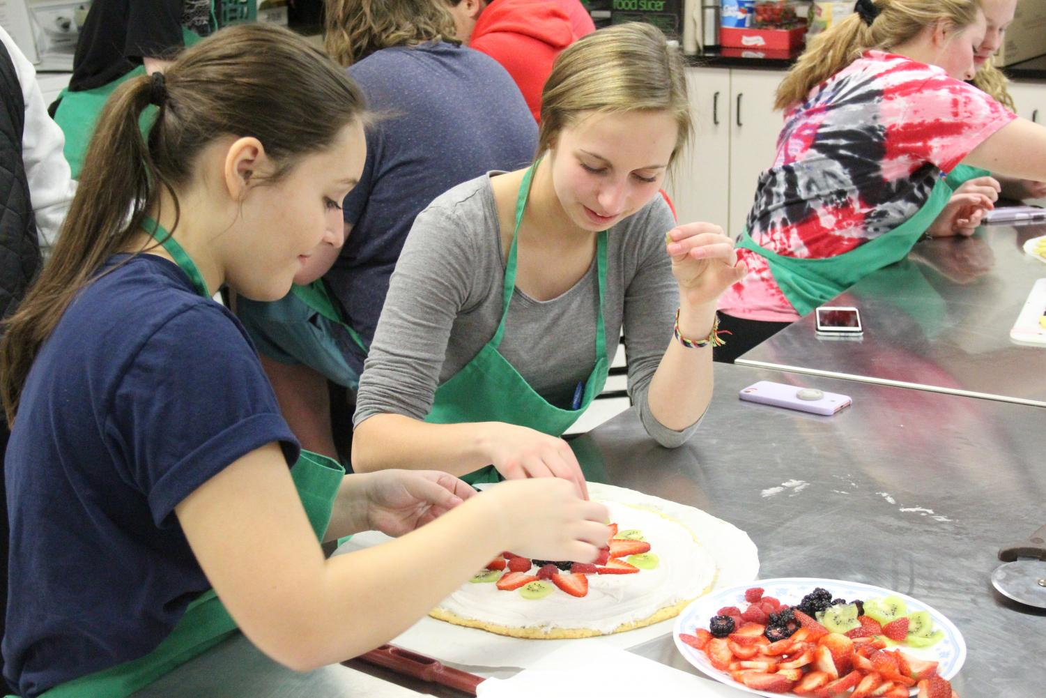 Sophomores Brailee Sanchez and Lizzie Metz decorate their dessert. Students enrolled in Foods II DE class can earn two credits for Northcentral Technical College.