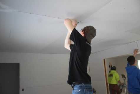 A student hammers nails into the ceiling for the new house.