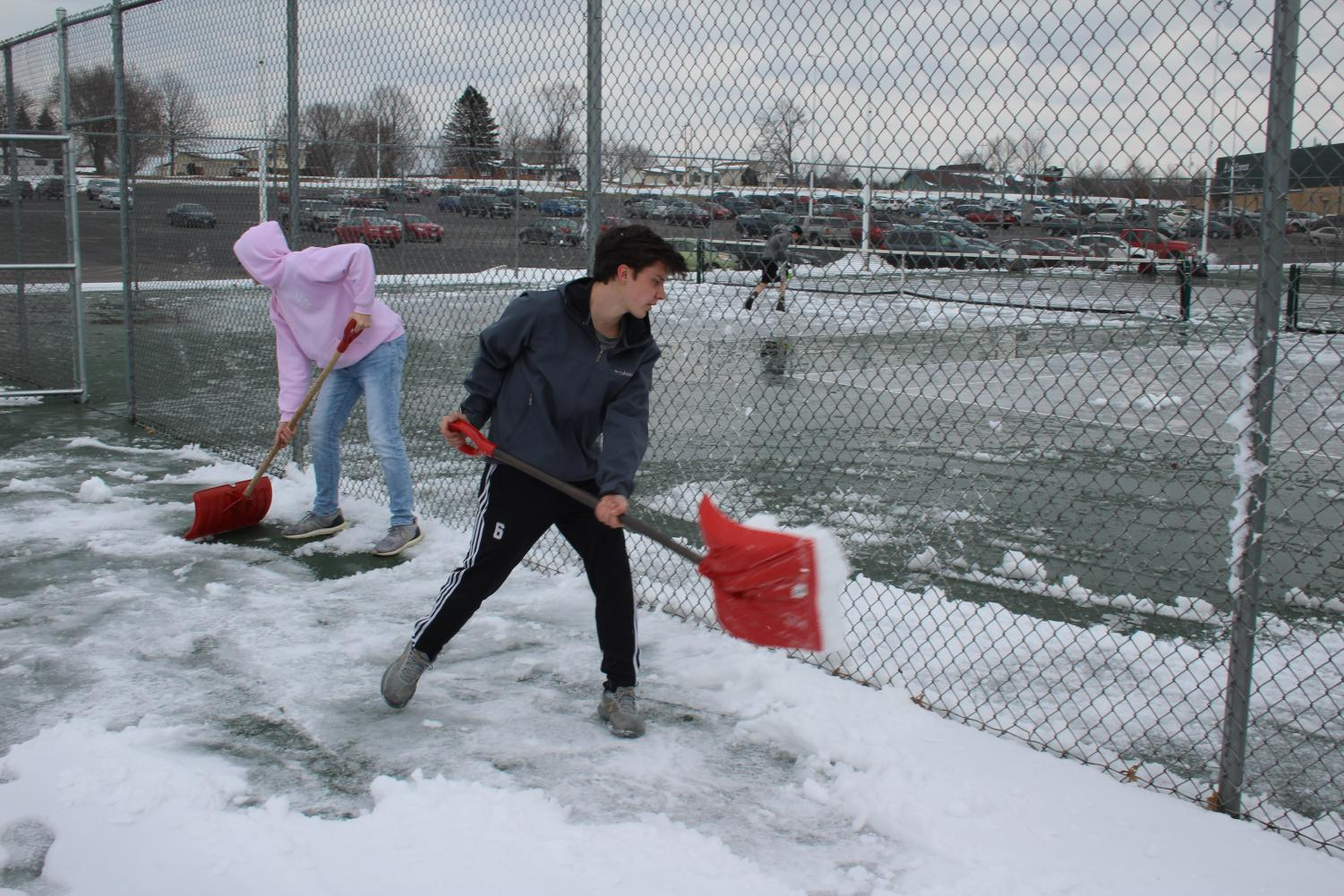 Jordan Sazama, senior, and John Belton, freshman, clear the courts full of snow after a snow day.